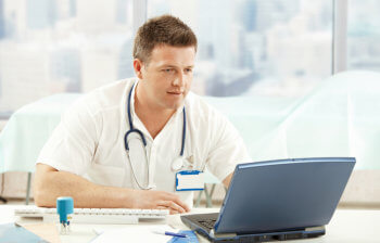 healthcare professional using a laptop
